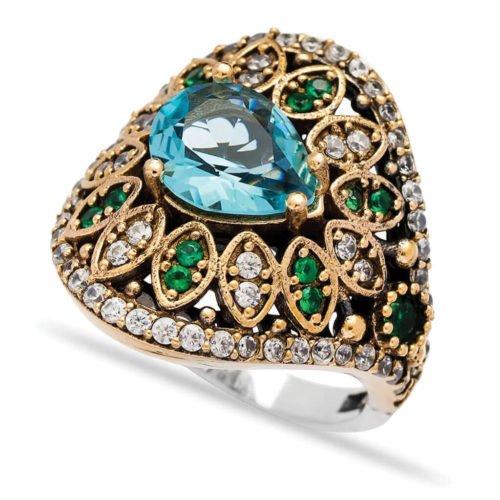 Ażurowy pierścionek z błękitnym topazem i szmaragdami